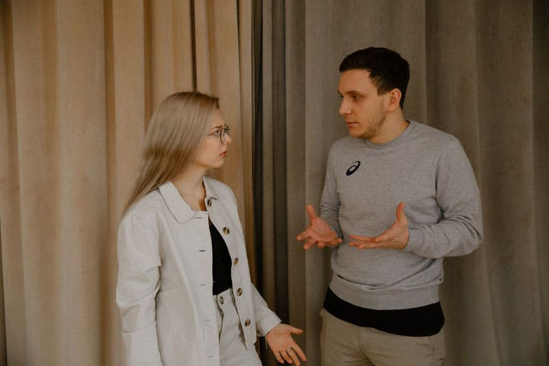 a couple arguing near a beige and gray curtains