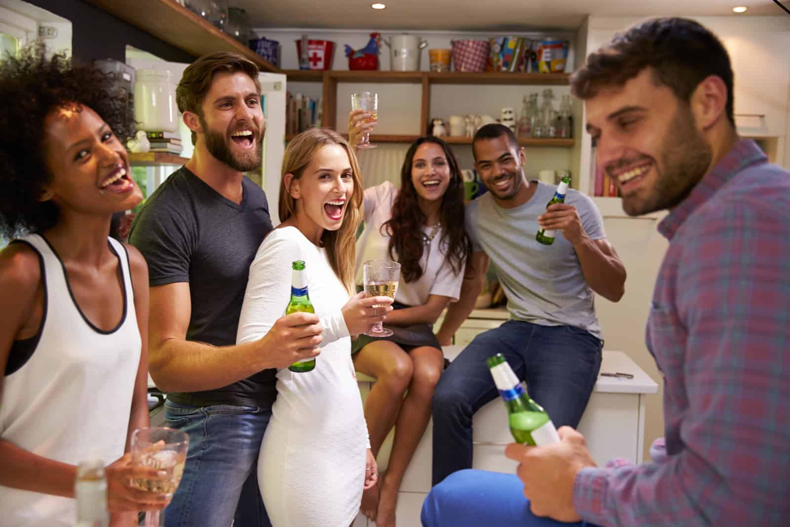a group of cheerful friends have fun at home with alcohol