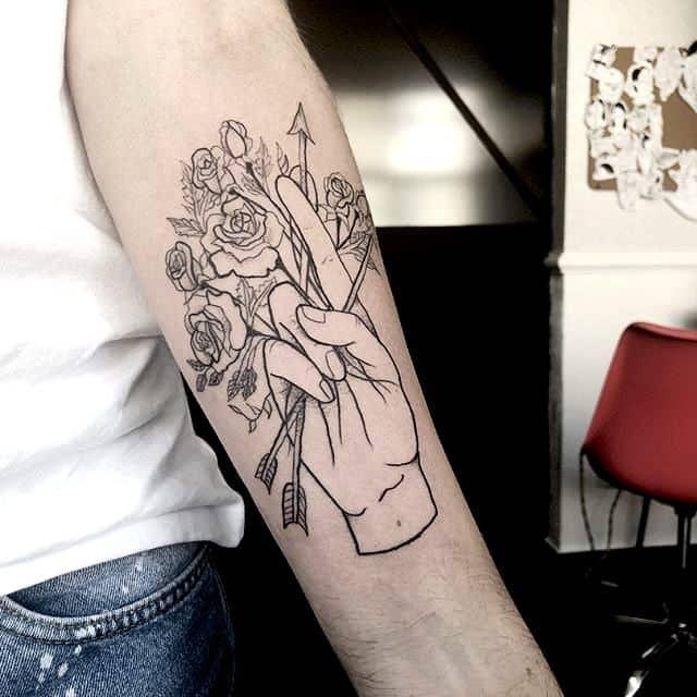 A hand holding arrowand flowers tattoo on the arm