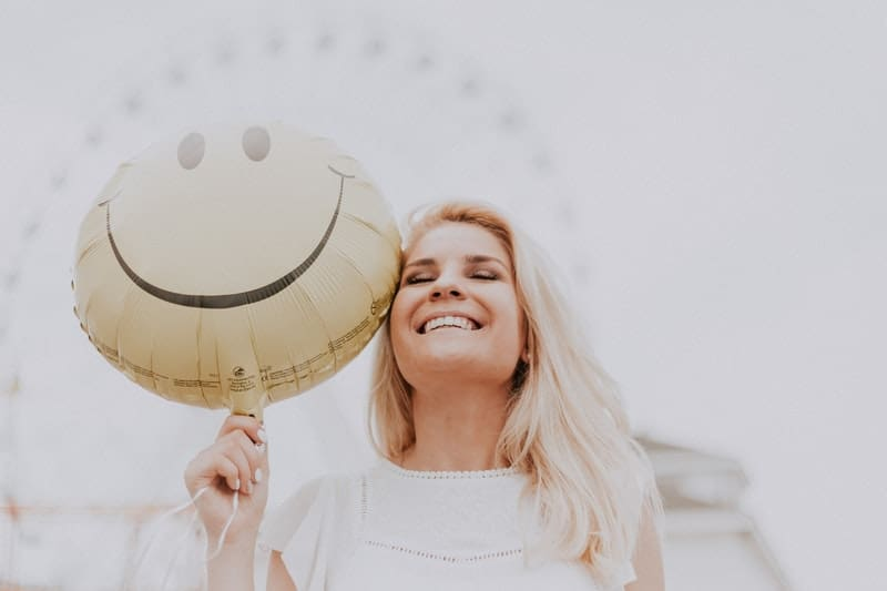 a happy woman bringing a smiley faced balloon