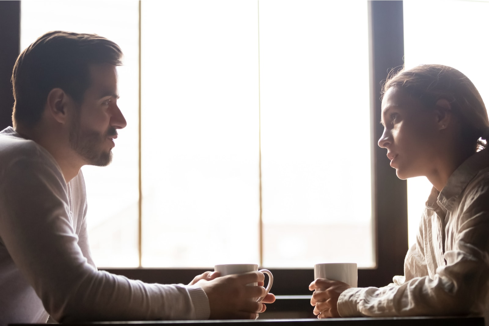 a man and a woman sit facing each other and talk