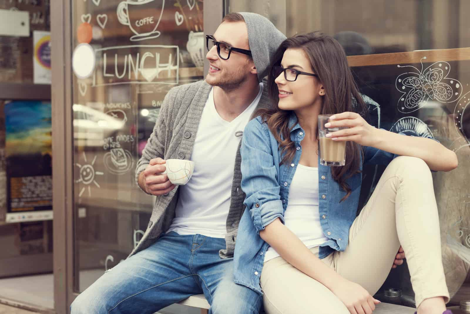 a smiling couple sitting drinking coffee and looking away