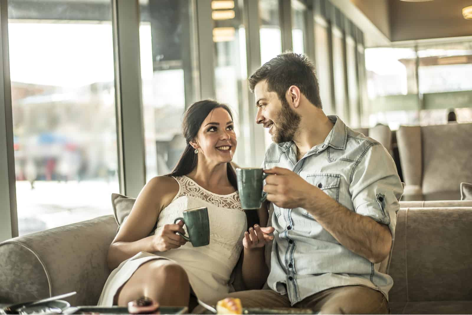 a smiling man and woman sit on the couch and drink coffee