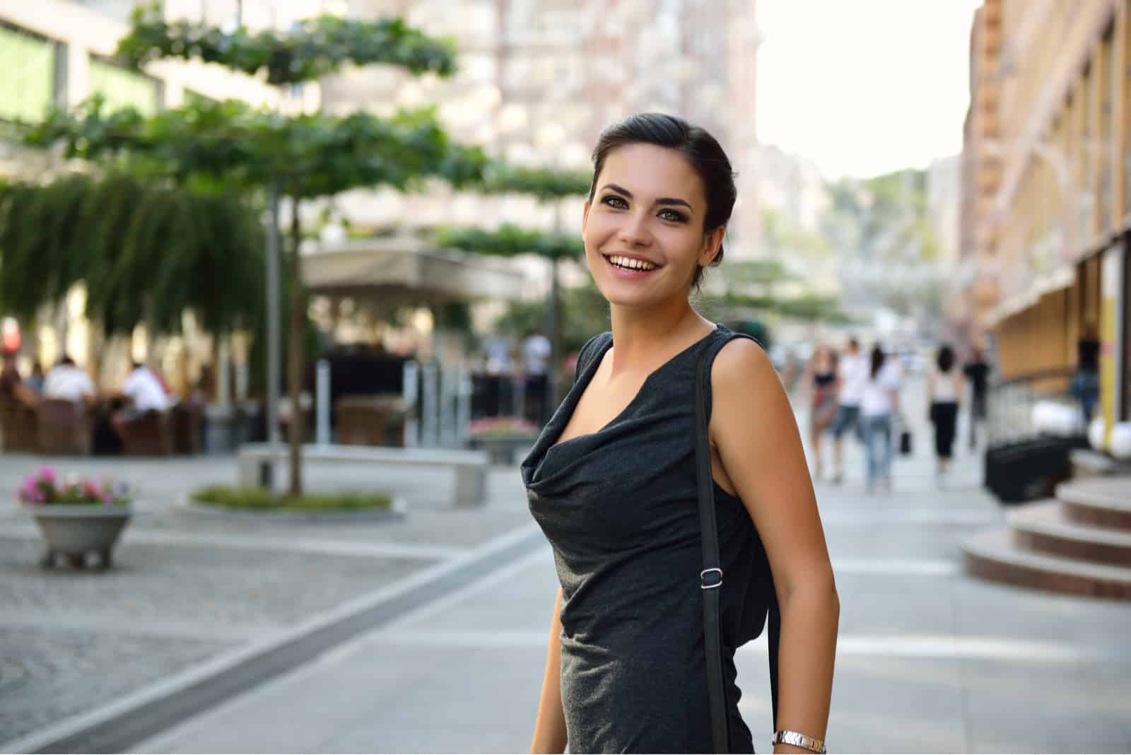 a smiling woman stands in the street