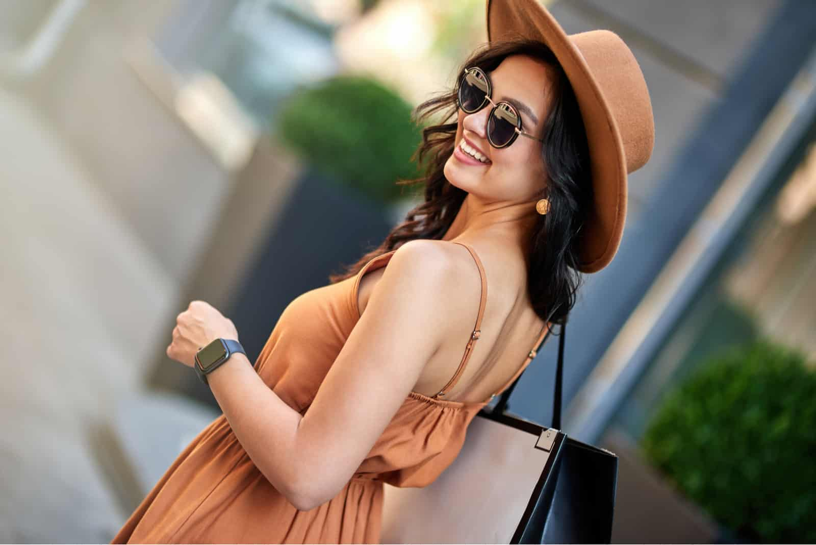 a smiling woman with a brown hat on her head walks down the street