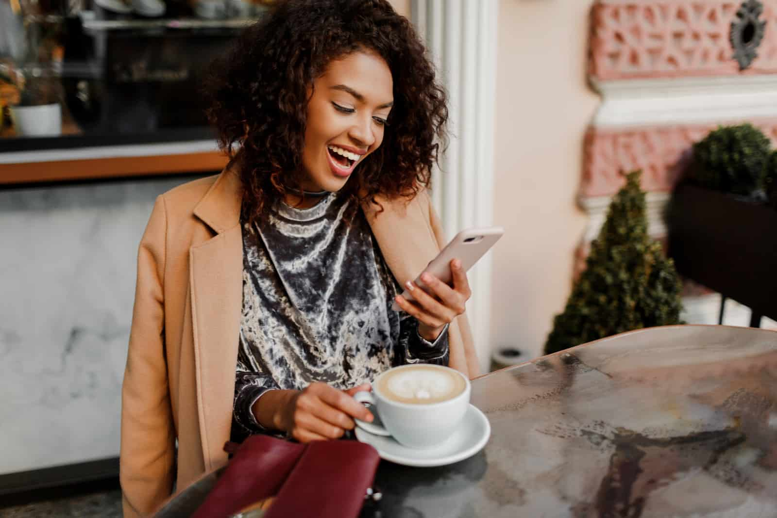a smiling woman with frizzy hair laughs and keys on the phone