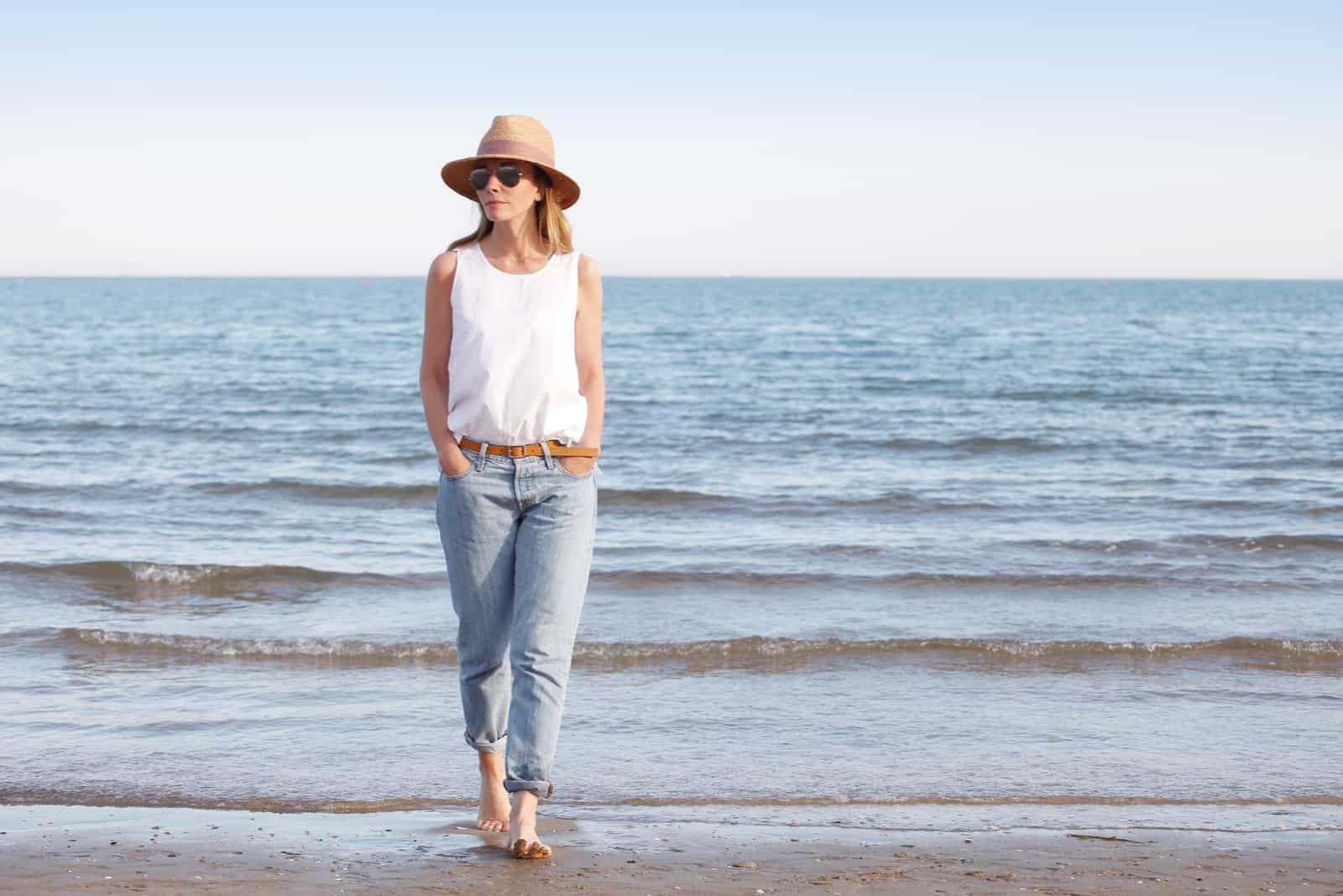 a woman with a hat on her head sets the beach