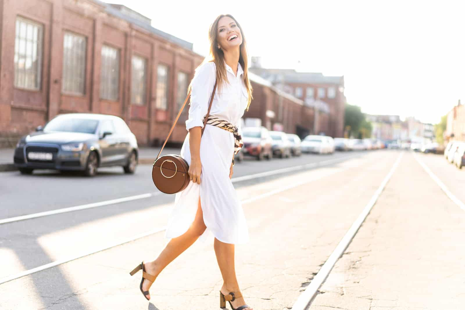 a woman with long brown hair in a white dress walks down the street