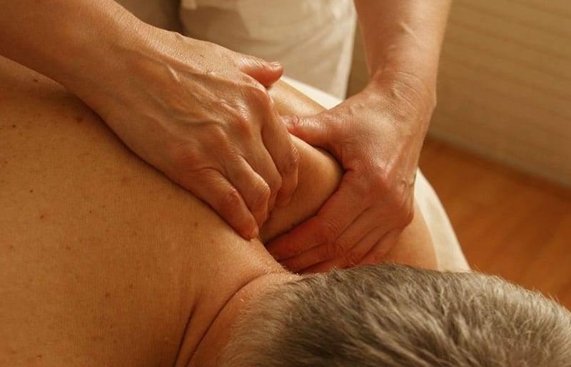 adult hand massaging the shoulders of an adult man