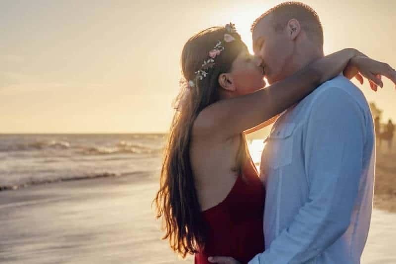 affection backlit beach couple kissing