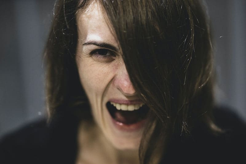 an angry woman half of the face covered with hair focused
