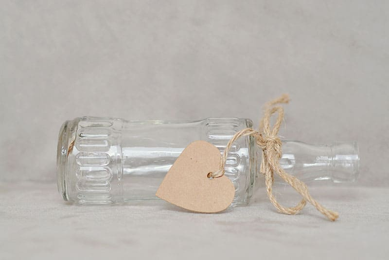 an empty bottle laid down with ribbon and heart shaped cardboard
