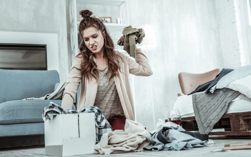 Angry young woman getting rid of her ex things