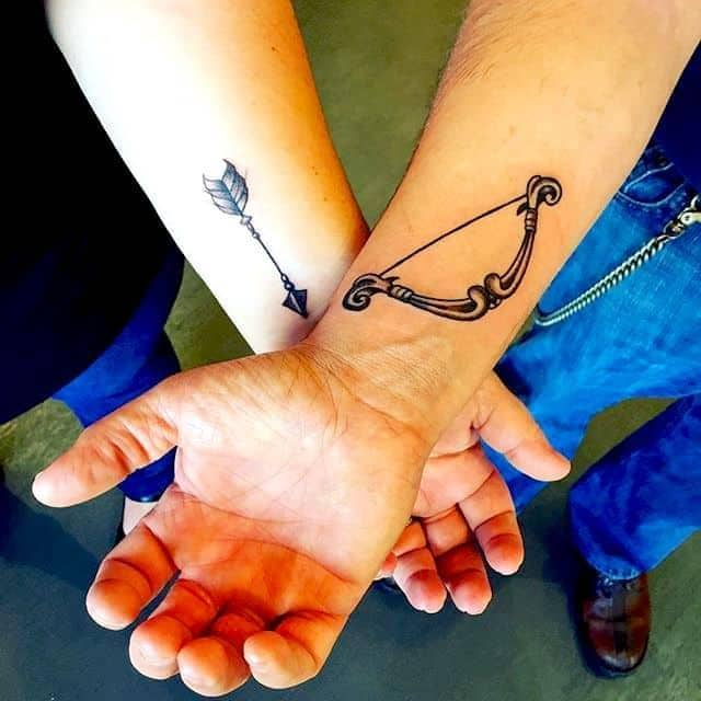 arrow and bow matching couple tattoos on two persons wrist
