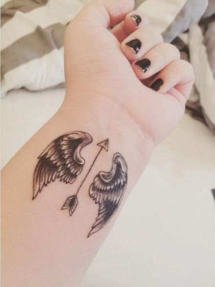 arrow with angel wing tattoo on the wrist