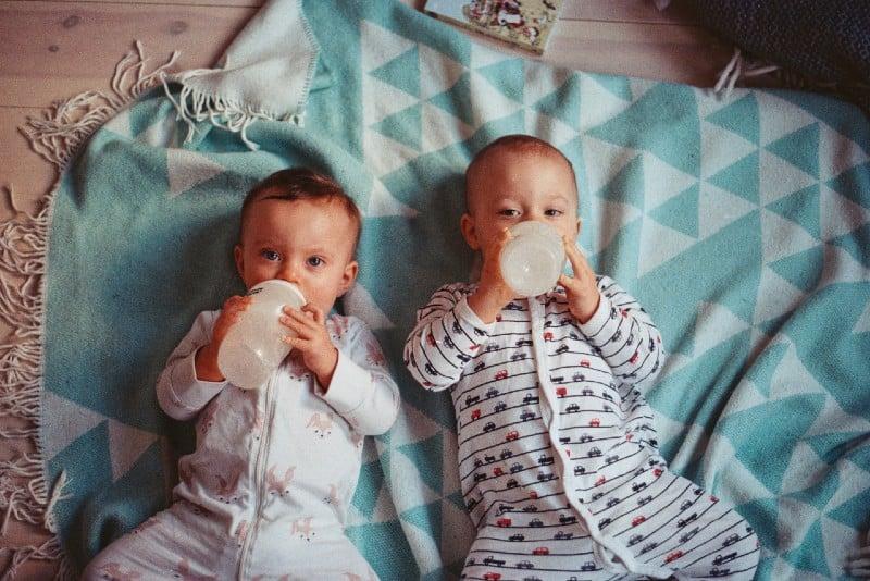 male twin babies lying on blue blanket