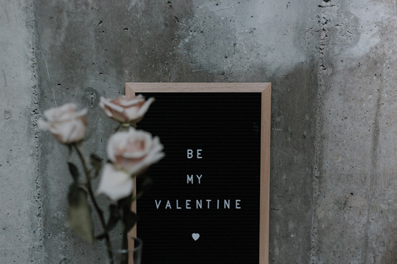 be my valentine message on black board with roses beside