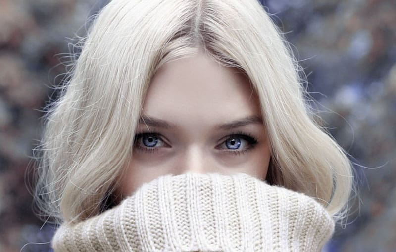 beautiful blond woman covering her mouth with her sweater in focus photography