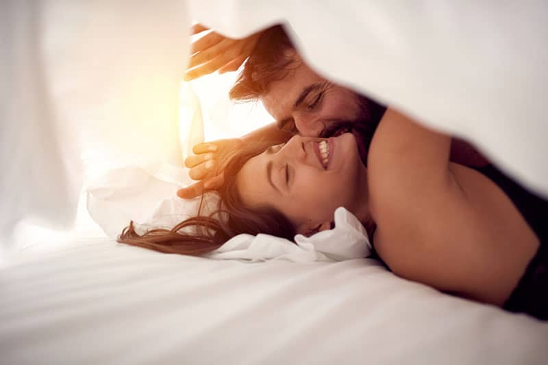 beautiful couple kissing under the sheets