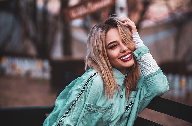 beautiful smiling woman leaning on bench wearing denim jacket