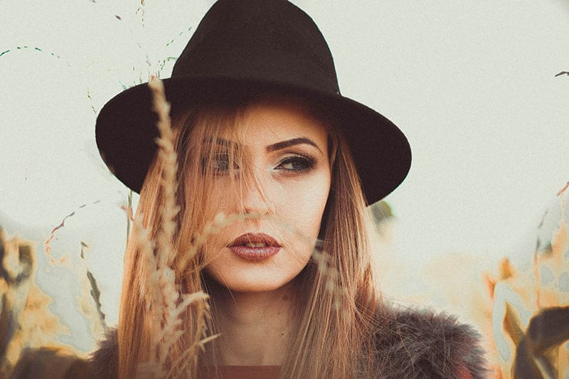 beautiful woman with hat with tall grass in front of her
