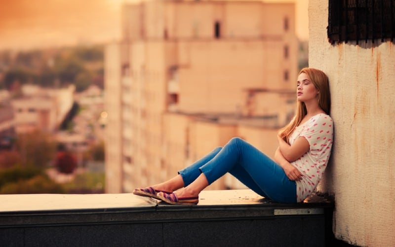 beautiful young girl sitting on the roof during daytime