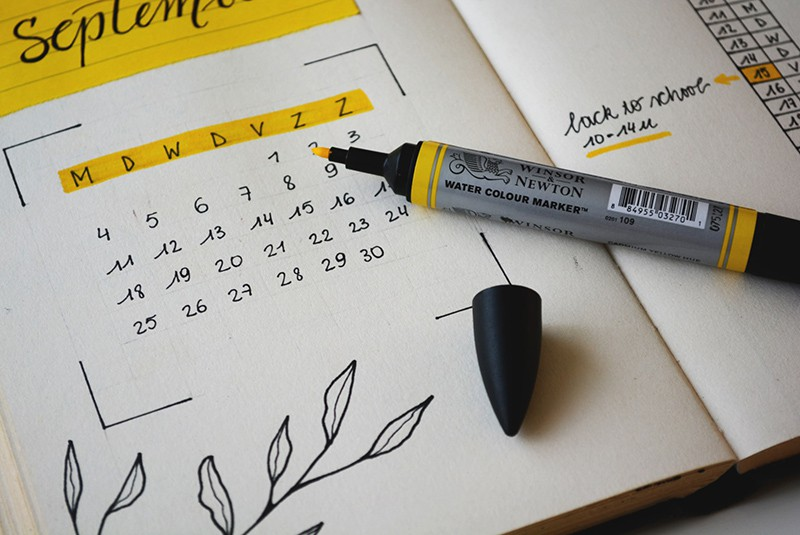black marker on notebook with calendar on it