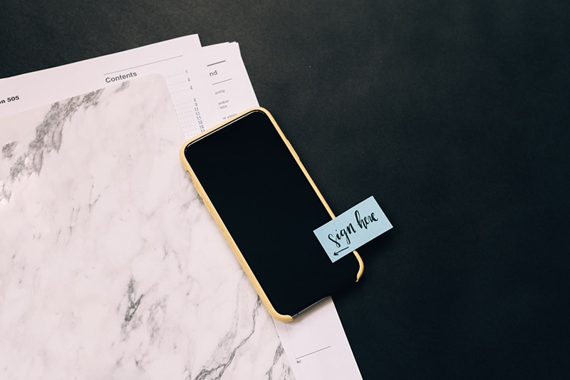 black smartphone on white pad with sticky note on it