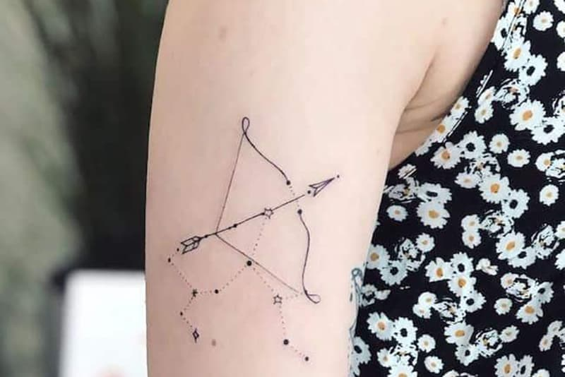 bow and arrow with sagittarius constellation tattoo on the shoulder