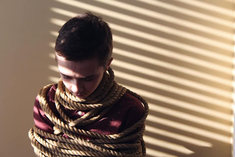 boy tied with a rope with shadows of the blinds from a window