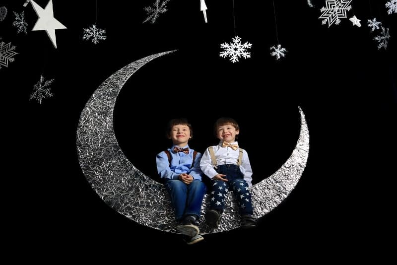 two boys sitting on crescent moon