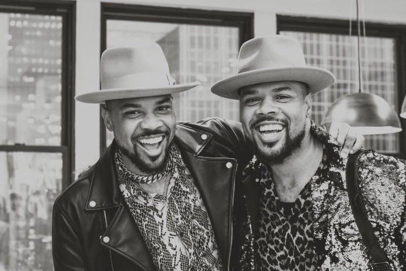 male twins with fedora hats standing indoor