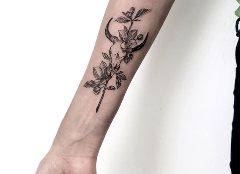 bull scull tattoo with flowers on the wrist