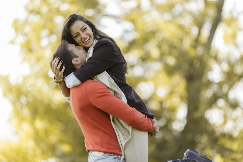 cheerful couple hugging outside in nature
