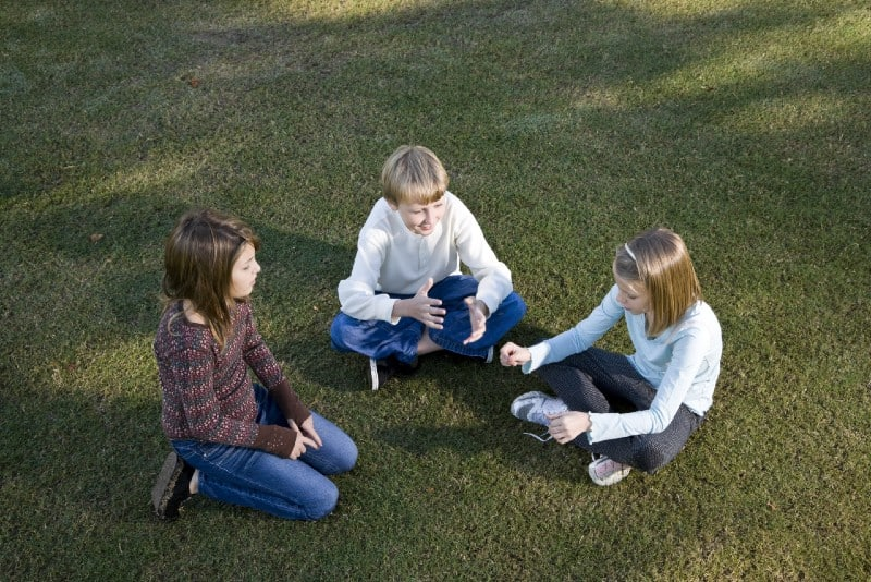 three kids sitting on grass and talking