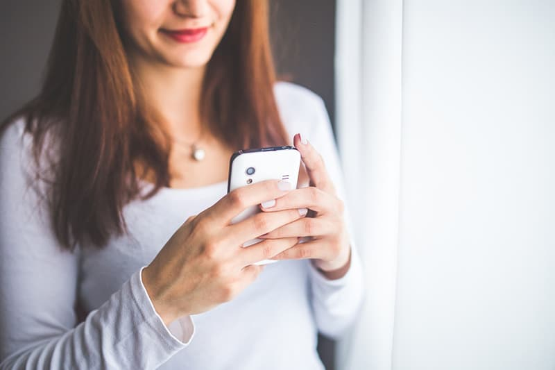 Close up of a woman smiling while texting