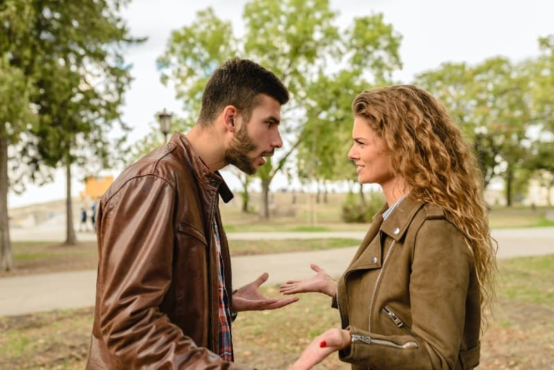 man and woman in brown leather jackets arguing