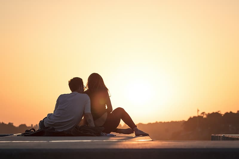 Couple sitting down on cement floow while gazing at the sunset