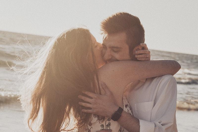 Couple by the beach hugging cheek to cheek