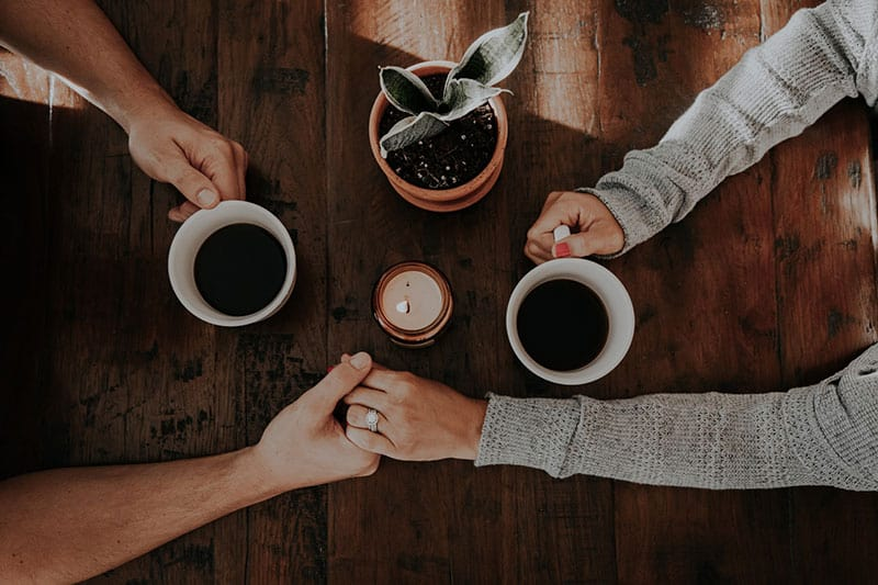 Couple's clasped hands and holding coffee mugs