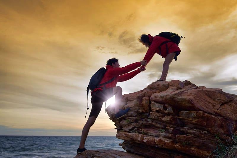 Couple climbing mountain during sunset