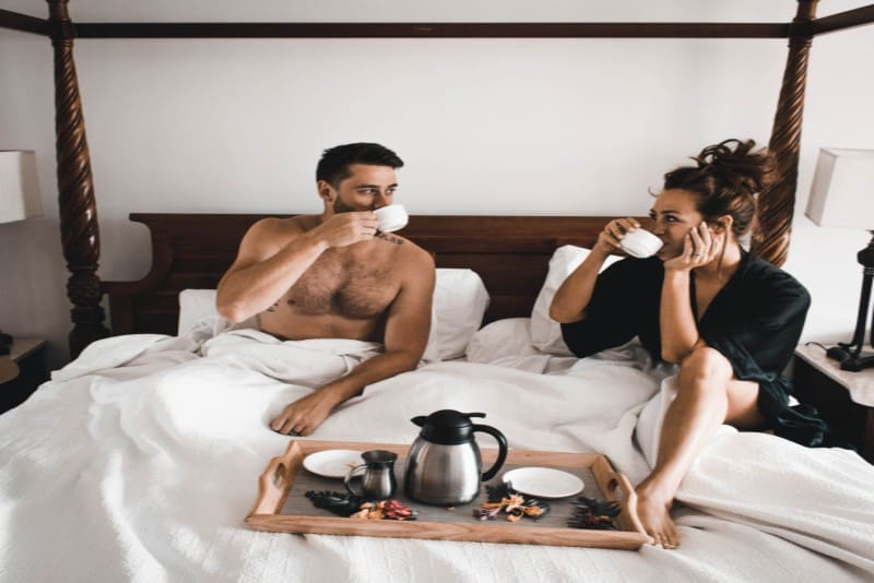 man and woman drinking coffee in bed
