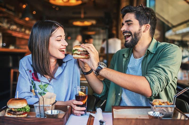 Couple breakfast man serves burger to woman
