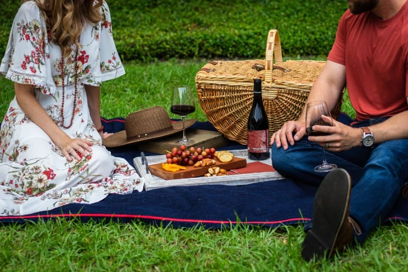 man and woman sitting on blue textile beside picnic basket
