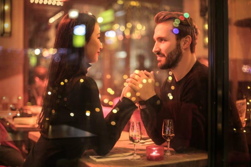 woman and man holding hands near two glasses at restaurant