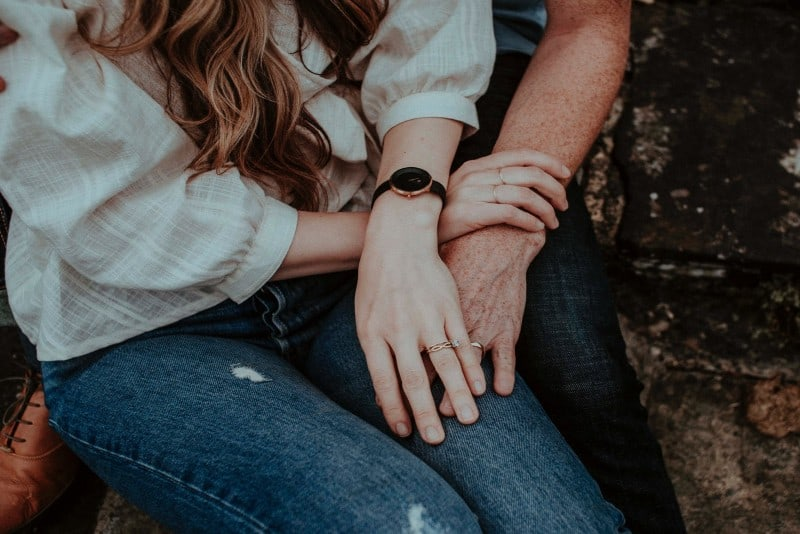 couple with wedding rings holding hands