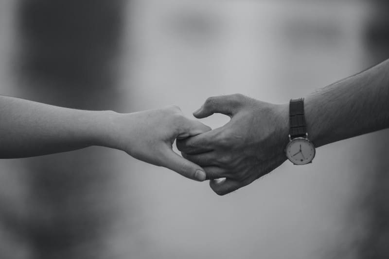 monochrome photo of man and woman holding hands