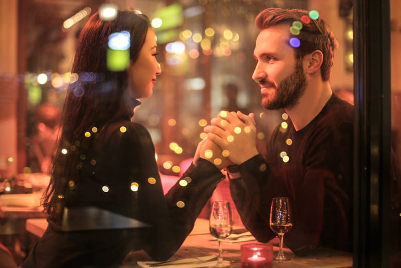 couple holding hands near the window in the restaurant