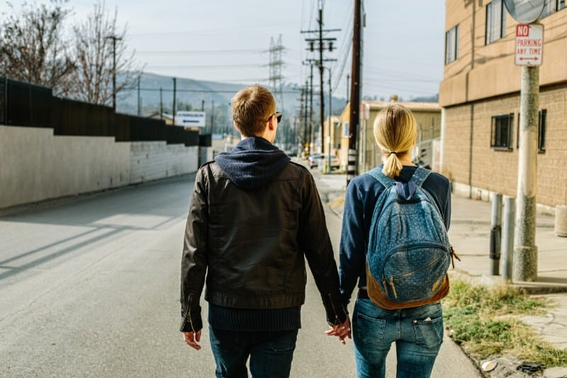 man and woman holding hands and walking on concrete road