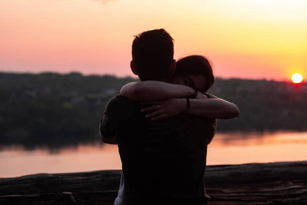 couple hugging each other during sunset